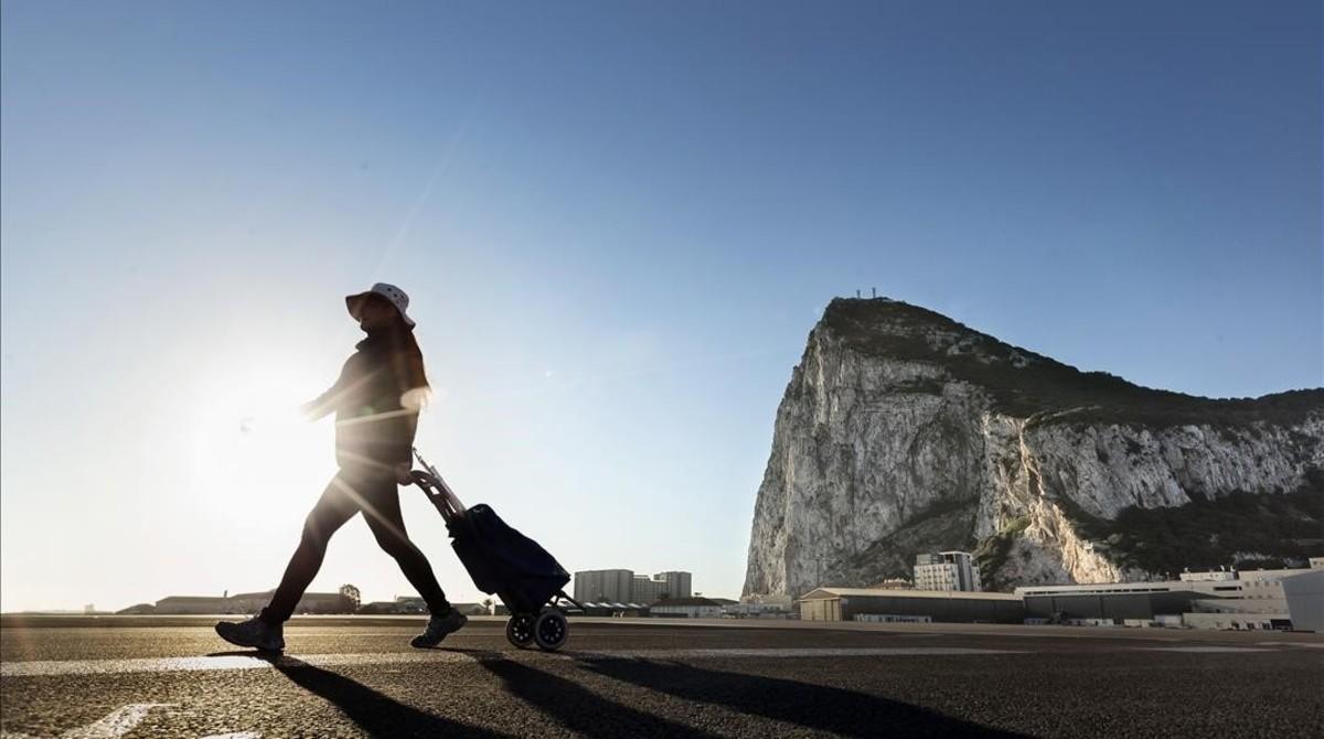 Una mujer camina por el lado español de la frontera entre España y Gibraltar, con el Peñón al fondo, en La línea de la Concepción, el 1 de marzo.