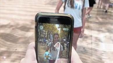 Dos j�venes utilizan la aplicaci�n Pok�mon Go en la Rambla.