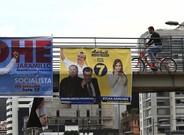 Ciudadanos caminan frente a varios carteles electorales en Quito.