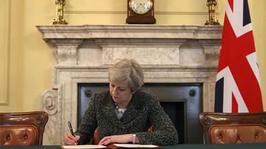 La primera ministra británica, Theresa May, firma la carta con la que arranca el 'brexit'.