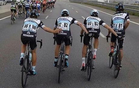 Rigoberto Urán (dreta) orina en plena carrera mentre els seus companys {le} ajuden a mantenir l'equilibri, durant l'última etapa de la Volta a Catalunya