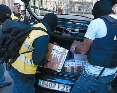 Varios agentes cargan en un coche documentos incautados en el Xaloc, ayer en Girona.