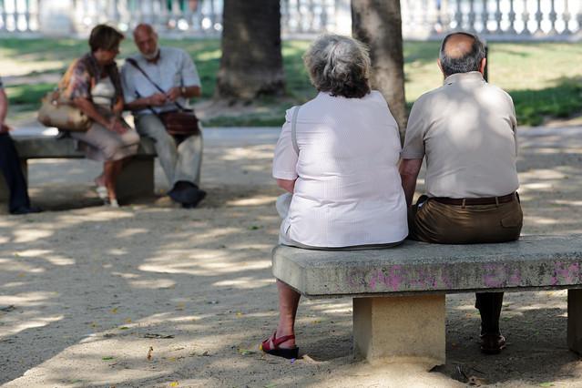 Un grupo de jubilados descansan sentados en unos bancos en una calle de Barcelona.