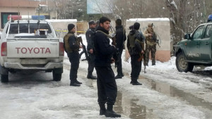 Afghan policemen keep watch at the site of a bomb blast in Kabul