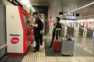 Unos turistas compran billetes en la estación de metro de Diagonal, ayer.