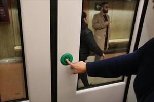 Una usuaria del metro de Barcelona acciona el mecanismo de apertura de puertas del vagón.