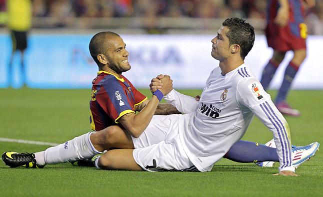 Dani Alves y Cristiano Ronaldo estrechan sus manos tras un lance del juego.