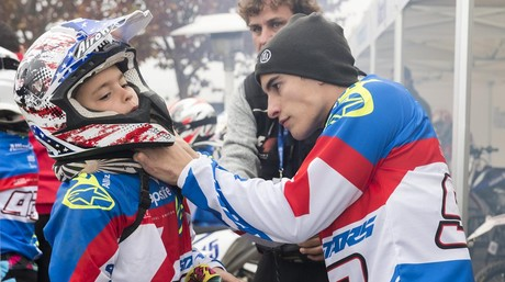 Marc M�rquez ayuda a un ni�o a colocarse el casco en el circuito de Rufea.
