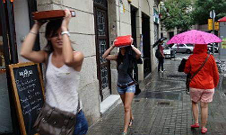 Unes noies es protegeixen de la pluja amb paraigua i llibres, a Barcelona.