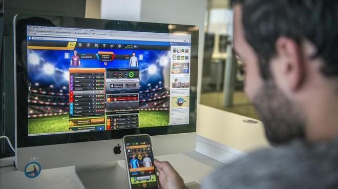Un usuario con un móvil y un ordenador con videojuegos en pantalla.