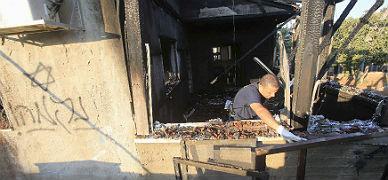 Un agente inspecciona la casa quemada, en cuya pared los atacantes pintaron un mensaje en hebreo.