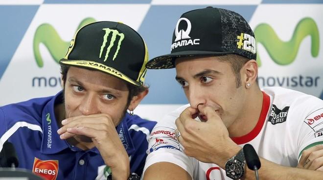 Andrea Iannone, derecha, dialoga con Valentino Rossi.