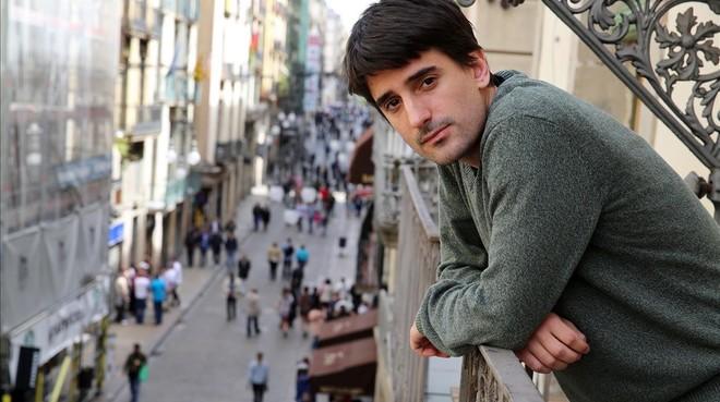 Denís Nadal, en el balcón de la habitación por la que paga 450euros al mes, en la que viven tres personas,con vistas a la calle de Ferran.