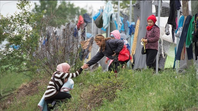 Una refugiada con su beb� en brazos, ayudada por otra a subir una colina en un campo cerca de Idomeni (Grecia), este mi�rcoles.