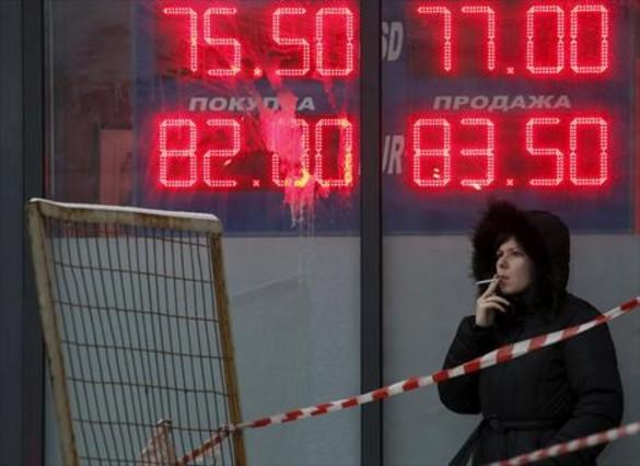 Incertidumbre 8Una mujer, ante un panel que muestra el cambio del rublo ante el euro y el dólar, en Moscú.