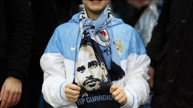 Una aficionada del Manchester City con una bufanda de Guardiola, vendida en las afueras del Etihad.