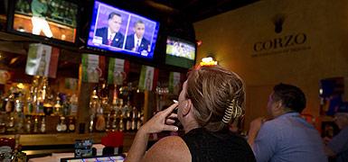Dos ciudadanos siguen el debate entre Barack Obama y Mitt Romney, anoche, en un bar de Las Vegas. AP
