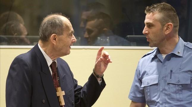 Tolimir (izq), condenado por la masacre de Srebrenica, habla con un guardia de seguridad de la ONU en el tribunal de La Haya, el pasado 8 de abril.