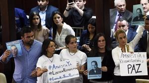 Diputados antichavistas, entre ellos Lilian Tintori (derecha), esposa del opositor encarcelado Leopoldo López, sostienen carteles a favor de la amnistía de los disidentes, en Caracas, este martes.