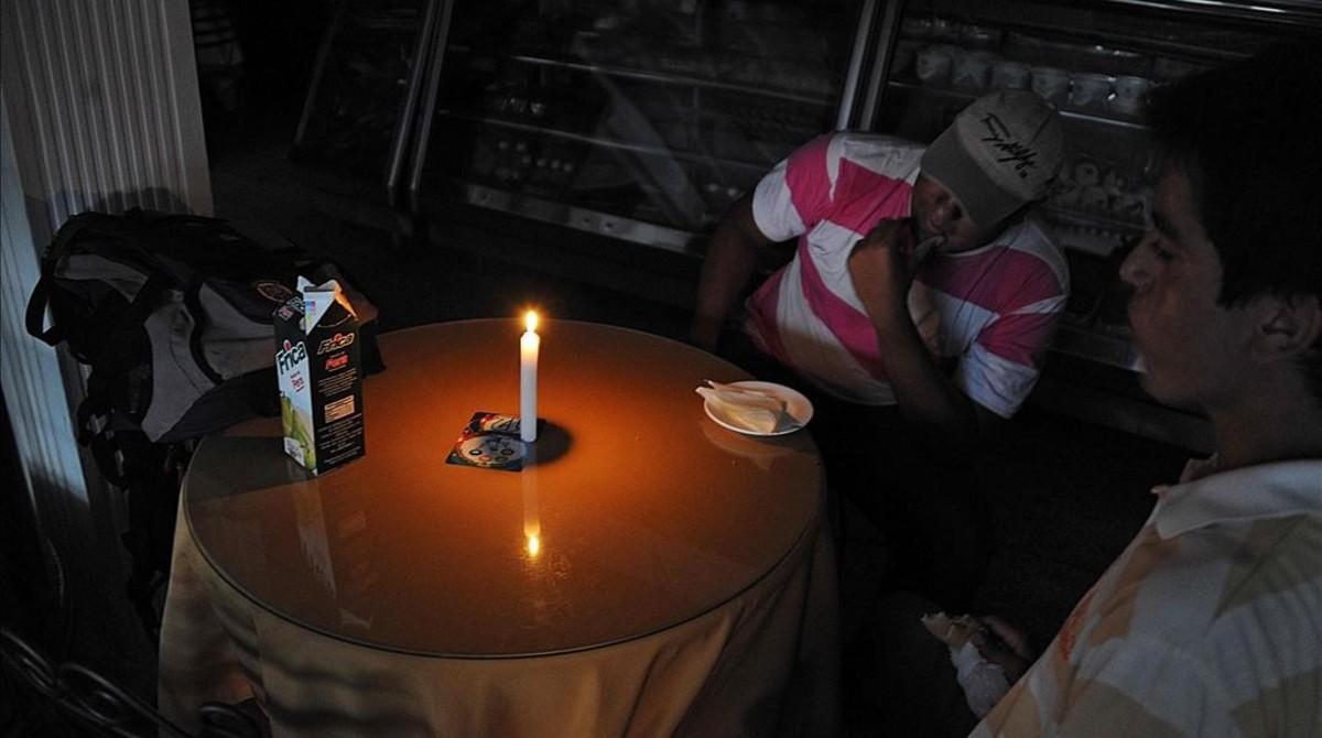 Hombres sentados en una panadería en San Cristóbal, a 600 kilómetros al oeste de Caracas, el 25 de abril.