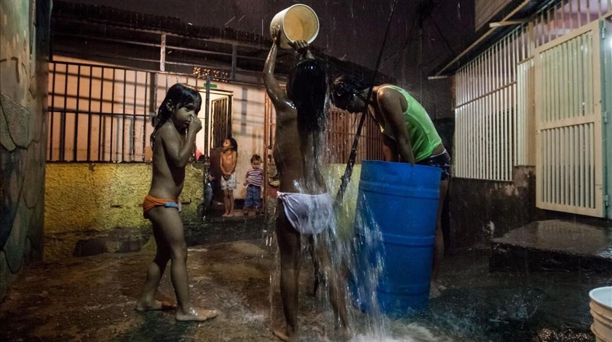 Un grupo de niños se bañan con agua de lluvia en un callejón de La Bombilla, en la favela de Petare (Caracas), el 22 de abril.