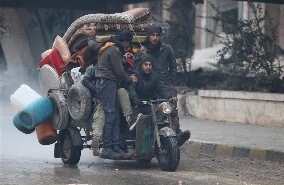 Ciudadanos de la ciudad síria de Alepo huyen en un triciclo de las zonas en combate.