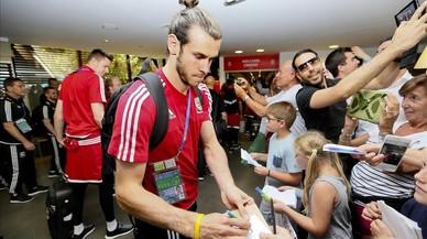 Bale firma autógrafos a unos aficionados galeses.