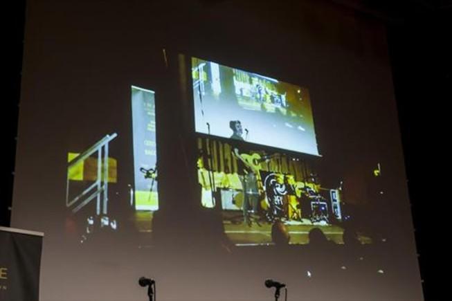 En pantalla, reproducción de lo que se estaba viendo desde unas HoloLens: el cantante de Ofiura en formato holograma en el escenario vacío de la Antiga Fàbrica Damm.