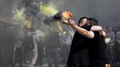 Dos taxistas se abrazan en Sant Jaume al tiempo que sostienen una bengala, en la manifestación de marzo.