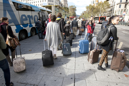 Varios turistas esperan transporte en la plaza de Catalunya de Barcelona.