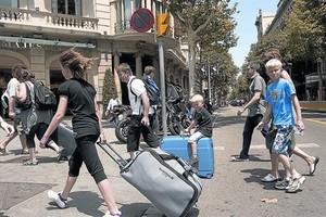 Turistes amb maletes rumb al seu allotjament, al passeig de Gràcia.