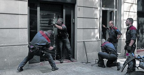 Unos mossosd'esquadraderriban la puerta del club cann�bico Hardala en la calle de Bail�n de Barcelona, ayer.