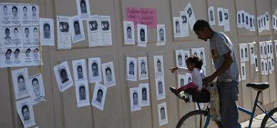 Una ni�a se�ala fotos de los estudiantes desaparecidos, el jueves en Ciudad Ju�rez.