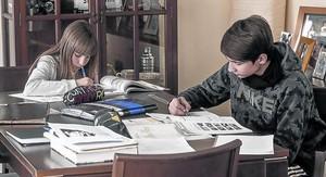 Dos hermanos hacen deberes en casa, ayer.