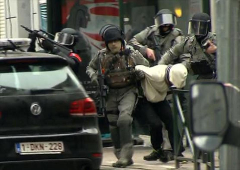 Un sospechoso es conducido por la policía en el barrio de Molenbeek (Bruselas), ayer.
