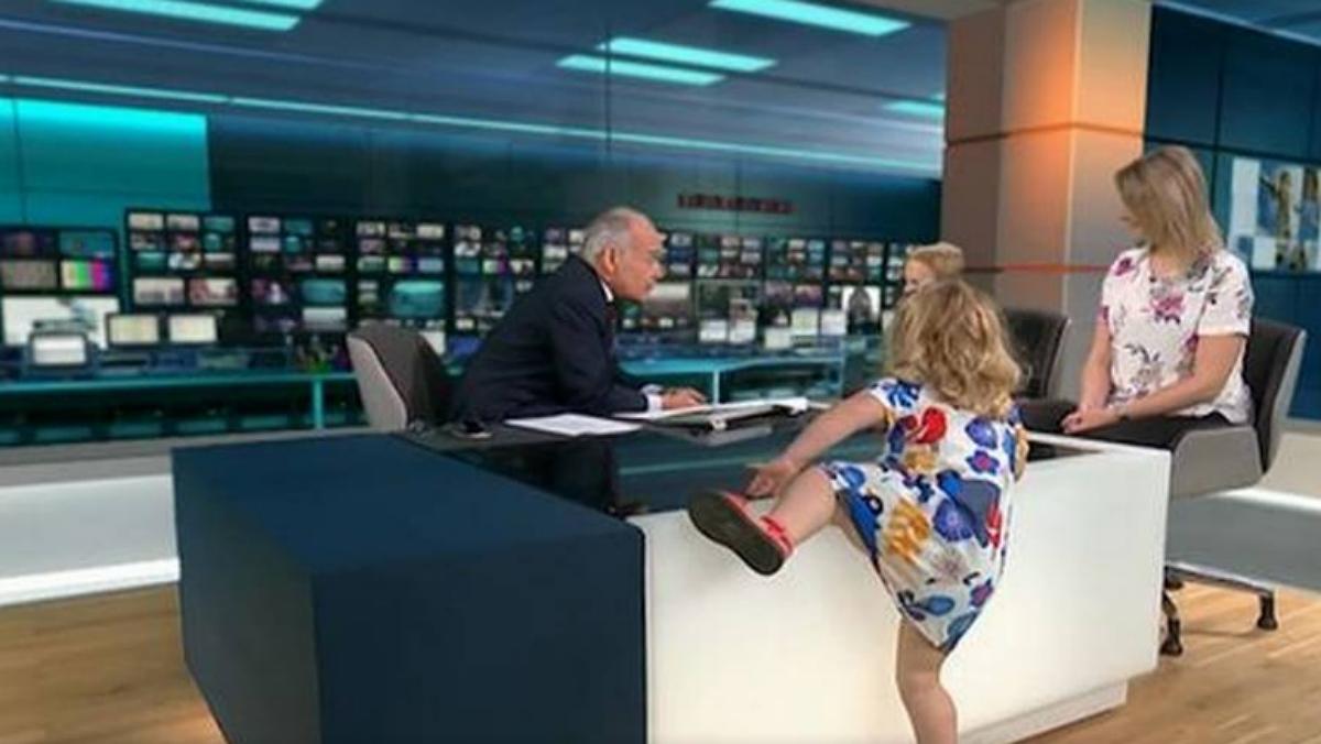 Una niña juega a subirse a la mesa de un presentador de televisión en directo
