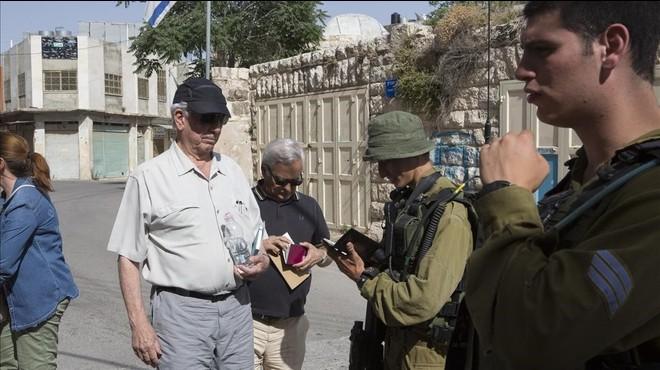 Soldados israel�s revisan el pasaporte de Mario Vargas Llosa en un control militar en la ciudad palestina de Hebr�n.