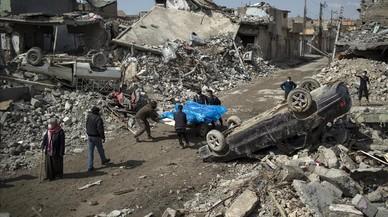 Unos civiles retiran cadáveres de entre las ruinas de Mosul.
