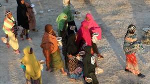 Unos inmigrantes caminan tras recibir comida en un centro de detención en Sabratha, el pasado 9 de octubre.