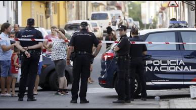 Agentes de policía y vecinos, frente al domicilio donde un hombre ha matado a su expareja, en Sevilla.