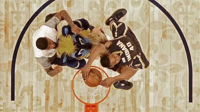 Glenn Robinson III salta por encima de Paul George (2,06), la mascota de los Pacers y una animadora del equipo para ganar el concurso de mates del All Star de Nueva Orleans.