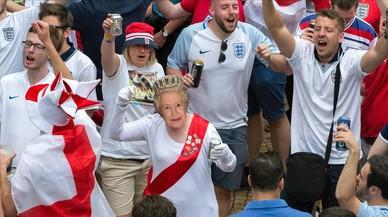Unos hinchas ingleses con la imagen de la reina beben las calles.