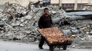 Un ciudadano de Alepo recoge escombros.