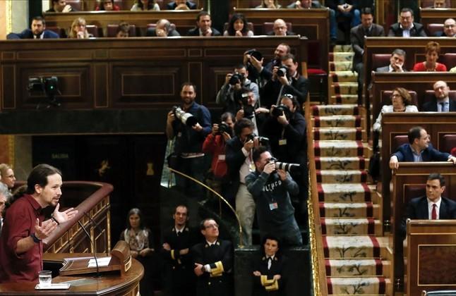 Pablo Iglesias se dirige al hemiciclo en la segunda sesión del debate de investidura con Pedro Sánchez sentado en su escaño.