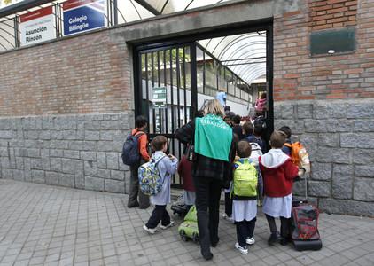 Pares i nens, a l'entrada d'una escola de Madrid, aquest dijous.