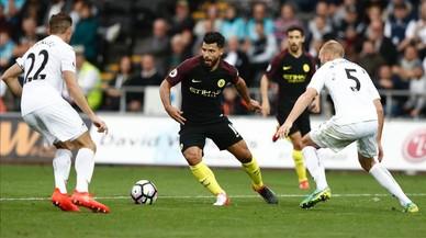 Ag�ero, entre dos rivales, en el partido del City ante el Swansea.