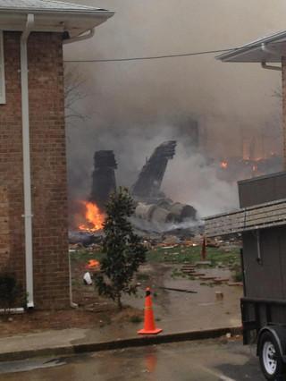 El fuselaje del avión siniestrado arde en el patio de una vivienda. AP