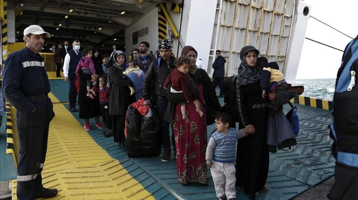 Refugiados y migrantes desembarcan del ferri Eleftherios Venizelos a su llegada al puerto de Elefsina, a 20 kilómetros al noroeste de Atenas, procedentes de Lesbos, este lunes.