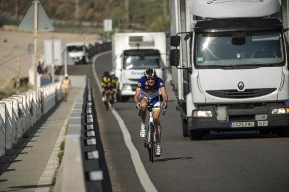 Dos camiones adelantan a unos ciclistas en la N-2 a su paso por Calella.