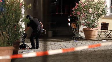 Un agente examina la mochila en la que el autor del ataque llevaba los explosivos, frente a un restaurante de Ansbach (Alemania), este domingo.